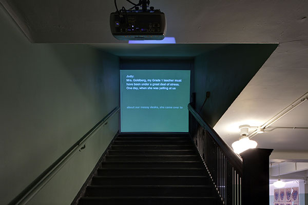 Installation view, looking up at left staircase projection screen